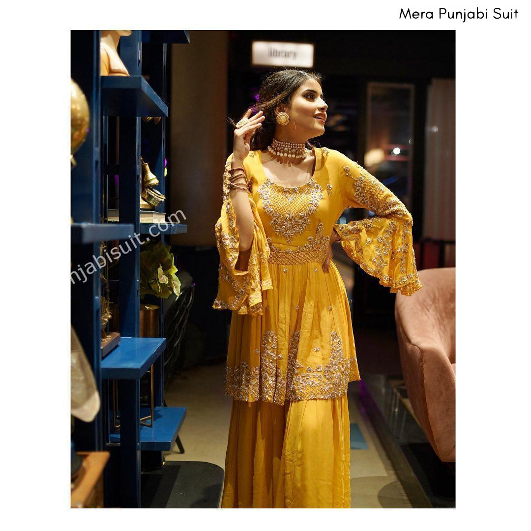 yellow peplum styled medium length embroidered anarkali with sharara and bell sleeves - heavy wedding guest look punjabi